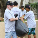 Pacxa President and CEO Gordon Bruce pitches in to clean up Kamaliʻi Park