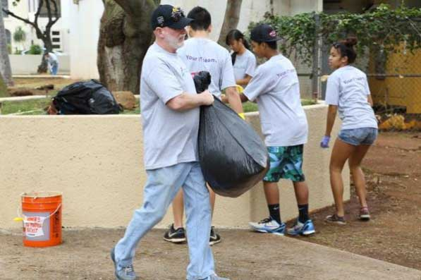 Gordon Bruce carrying trash bag with students in background at planter