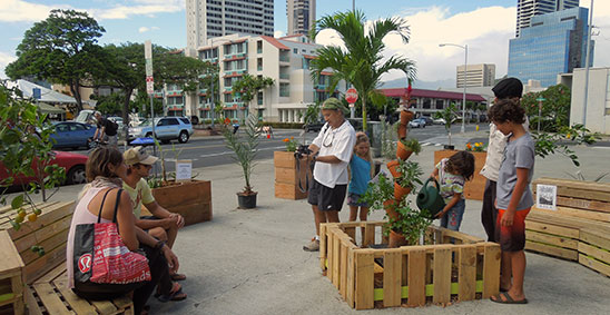 visitors relax on pallet furniture surrounded by plants