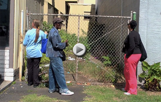 Three women inspect a small parcel of land behind a chain link fence.